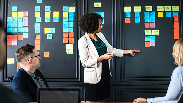 project leader standing at board with sticky notes