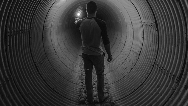 Man standing in dark tunnel and holding a lantern