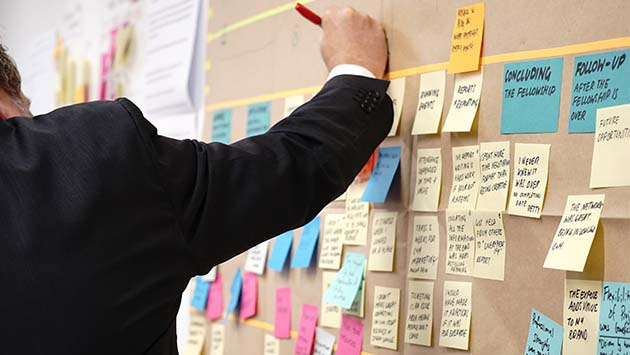 man writing on post-it notes on planning board